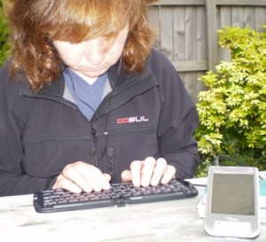 Picture of Cathy using her wireless micro keyboard to record journal on PDA.