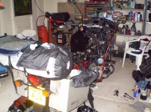 Picture of the bike in Cathy's garage with tools all over the floor. The petrol tank is off and various bits of wire are diconnected. At this point I am still looking for the problem!