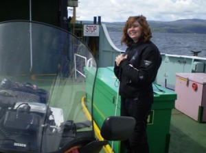 icture of Catherine staanding on the deck of the ferry from Tarbet to Portavadie as we crossed from Bute towards the ferry for Arran. The windshield of the bike is visible in the left hand side of the picture. In the background behind Cathy's head you can see the ocean.