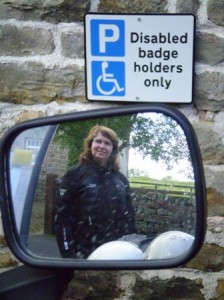 Picture taken of Catherine in the rear view mirror of the bike. On the wall above the mirror is the disabled parking bay wall plaque.
