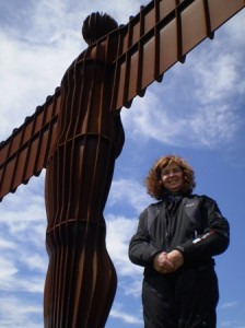 Picture of Cathy standing in the shadow of the Angel of the North towering above her.