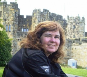 Picture of Cathy sitting at the entrance to the castle. Behind her is the gateway through which Harry made his entrance in the flying car and the gateway also featured in several other scenes. The walls of the castle are visible above her head.