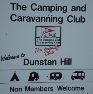 "Picture of the sign at the entrance to the campsite. The sign says ""The camping and caravanning club. The friendly club. Welcome to Dunstan Hill. Non-members welcome."