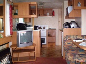 Picture of the inside area of the caravan. It shows the kitchen area with the microwave above the helmets on the right which Cathy tried to tune into BBC1.