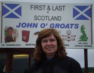 "Picture of Cathy standing before a sign at John O'Groats which says ""First and last in Scotland - John O'Groats"". The sign has the Scottish flag (white cross on blue background) on the top left and right corners."