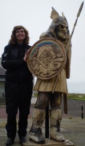 Picture of Cathy standing with our wooden friend 'Eric the Viking'. Eric is about 6 feet tall complete with shield on his right arm and holding a spear in his left hand pointing upwards to the sky. His helmet has wings on it.