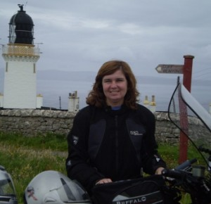 Picture of Cathy standing by the bike - in the foreground - with Dunnet Head lighthouse behind her and a signpost saying 'Cliff Viewpoint over her shoulder.