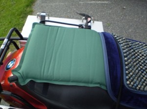 Picture of the air camping pillow attached to the pillion seat of the bike with the air valve in the bottom left hand side.