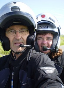 Picture of Bernard and Cathy looking at the camera while sat on the bike. Only their shoulders and heads are visible with the helmets on. Bernard took this photo by holding the camera at arms length. It took about 12 attempts to get one he liked!