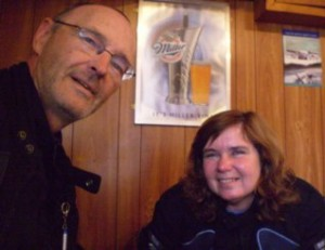 Picture of Cathy and Bernard in the pub in Tarbert where they drank many coffees before getting on the bike after their trip across the 'mountain goat road'. The mood is lighter and both are now smiling and Bernard has been acting daft to get Cathy to smile!