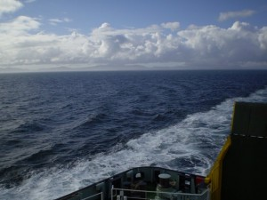 Picture of a very blue ocean with the wake of the boat showing white in the foregound. The sky is blue and the clouds are white. The loading ramp at the rear of the boat is just visible on the bottom right hand side of the picture.