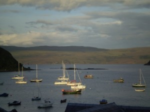 Picture of the harbour at Portree. In the foreground there are many small boats with masts visible. The mountains are in the mid-gound and a cloud filled sky shows grey and white in one of those changeable days which shifted between showers and sunshine.