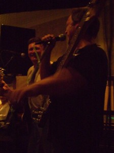 icture of the two lads in Shenanagin. The bass player is talking on the microphone while the guitarist looks sideways laughing at his colleague.