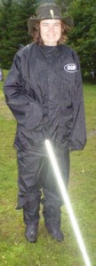 Picture of Cathy on the campsite at Ben Nevis. She has her waterproofs on and a wide brimmed waxed cotton hat on. He cane is lighting up like a light sabre in Star Wars due to the flashon the camera hitting the reflective materials.
