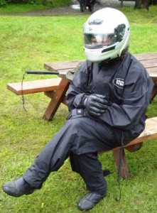 Picture of Cathy sitting on a picnic bench at the flooded campsite at Ben Nevis. She has all of her bike gear on - including silver helmet and bike gloves - due to the rain and she is actually laughing inside her helmet.