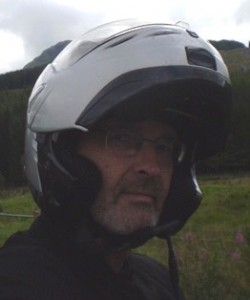 Picture of Bernard - with helmet on - looking sideways at camera. A week's worth of stubble is on his chin and he claims it was to keep his face warm!