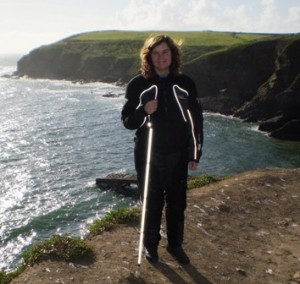 Picture of Cathy at the Lizard Point whith the cliffs behind her. The sea is in the background as is the other side of a cove which juts out into the sea. Her cane and motorbike clothes have caught the flash of the camera and that is why they are so white.
