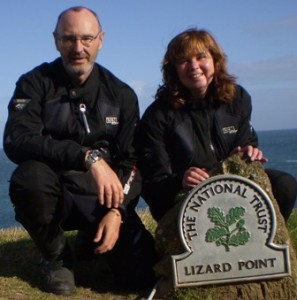 "Picture of Cathy and Bernard at the marker shield at the Lizard Point. The shield can be seen on the bottom right of the picture. It says ""The National Trust, Lizard Point""."