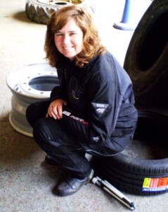 Picture of Cathy sitting on a tyre as she waits patiently for the new tyre. By her foot is her folded cane. As always, well nearly always, she is smiling.