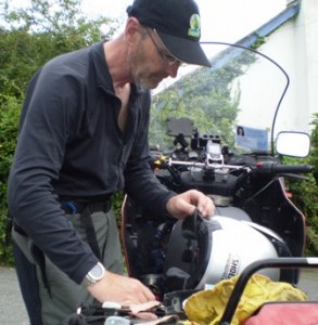 Picture of Bernard working on the wiring in Cathy's helmet. The helmet is sat on the bike and Bernard badly needs a shave.