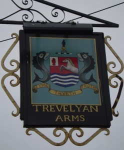 Picture of the hanging metal sign outside the pub. The sign has a coat of arms showing a shield with a white horse over waves. The shield itself has a fish either side of it - they look a little like sea-horses but not quite!