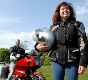 Picture of Cathy standing in front of the bike with Bernard sat on it and in the background.