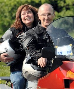 Picture of Bernard and Cathy sat on the bike with a disabled parking badge in the windshield.