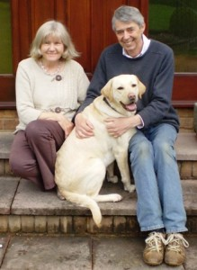 Picture of Sandra and Ian with Biscuit sitting on their front step.