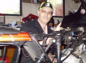 Picture of Bernard working on the bike with a big smile.