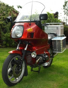 Picture of the red motorcycle named Bertha sat in the garden looking very shiny.