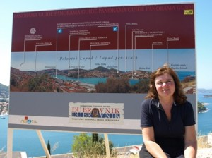 Picture of the layout of the new harbour at Dubrovnic shown on a large roadside board which Cathy is sitting in front of.