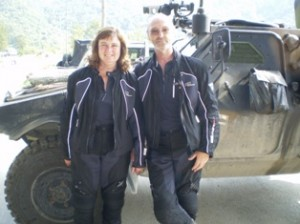 Picture of Cathy and Bernard standing in front of an armoured vehicle at the Kosovo border.