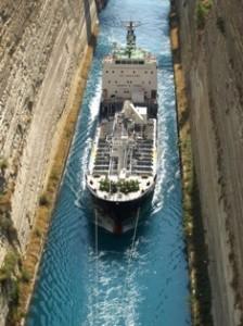 Picture of a large ship passing through the canal being towed by a tug.