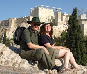 Picture of Cathy and Jim sitting on St.PAul's rock with the Acropolis in the background.