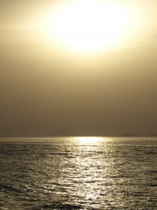 Picture of the sun setting over the ocean as night is falling.