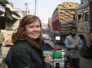 Picture of Cathy at the Nepal border surrounded by Indian Wagons. She has a very big grin on her face - we made it!