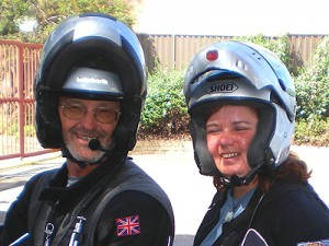Picture of Bernard and Cathy taken outside the Vision Australia office. It is a shoulders upwards shot taken while they are sitting on the bike - they are both laughing.