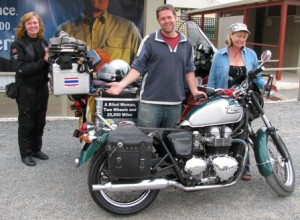 Picture of Greg and Diane standing by the defunct Triumph with Cathy standing in the background - the bike is British Racing Green and Silver.