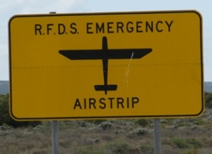 "Picture of the road sign declaring the road to be a ""Royal Flying Doctor Service Airstrip"""