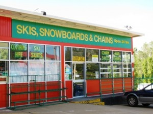 "Picture of one of the shops int he snowy mountains with the sign saying ""Skis, Snowboards and Chains"""