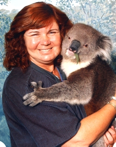 Picture of Cathy holding Peter while he munches contentedly on Eucalyptus leaves!