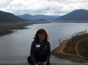 Picture of Cathy sat on the barrier at Dartmouth Dam with the water stretching off behind her.
