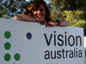 Picture of Cathy with  the sign board outside of Vision Australia.