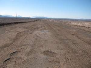 Picture of the old road. It is sand and dust as a base with small holes and ridges along its length.
