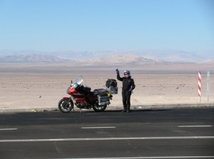 Picture of Cathy in the distance behind Bertha waving to the camer. Behind her is miles of sand whihc stretch towards some low hills.