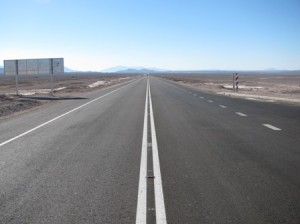 Picture taken in the middle of the road showing the white line going off as far as the horizon. In the far, far distance is a small mountain range.