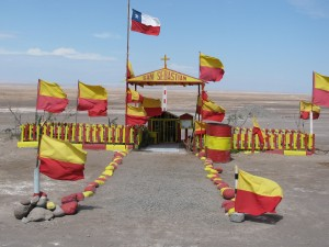 Picture of one of the shrines in the middle of nowhere. It has yello and red painted stones leading towards the entrance. The whole structure, including covered canopy, are in the national colours of Chile (yellow and red). Flags flutter in the breeze in the same colours. There is nothing else in the surroundings which stretch for miles.