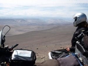 Picture of the bike and cathy looking off into the distance. The view stretches for miles in front of her and consists of rolling hills and sanad for as far as the eye can see.