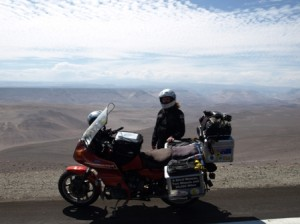 Picture of Cathy standing on the other side of the bike higher up in the Chilean mountains with them acting as a backdrop. White clouds cover the top half of the picture as we are at cloud level.