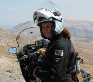 Picture of Cathy in her helmet looking over her left shoulder with the mountains in the background.
